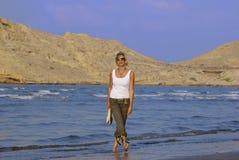 Giovane donna che cammina alla spiaggia Fotografie Stock Libere da Diritti