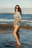 Giovane donna che cammina alla spiaggia Fotografie Stock