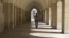 Giovane donna che cammina attraverso l'arco stock footage