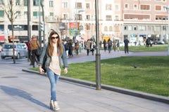 Giovane donna che cammina attraverso la folla sulla via. Fotografia Stock