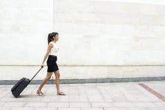 Giovane donna che cammina con i bagagli sui cenni storici della parete. Immagine Stock