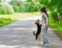 Giovane donna che cammina con il cane del cane da lepre fotografia stock