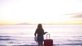 Giovane donna che cammina con una valigia sulla spiaggia stock footage