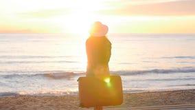 Giovane donna che cammina con una valigia sulla spiaggia video d archivio