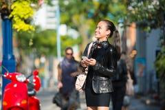 Giovane donna che cammina e che texting sul telefono astuto fotografia stock libera da diritti