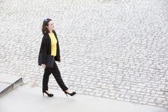 Giovane donna che cammina e che tiene un libro Immagini Stock Libere da Diritti