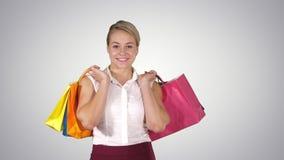Giovane donna che cammina e tenere i sacchetti della spesa mentre facendo una certa spesa, Alpha Channel stock footage