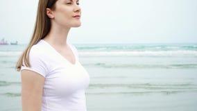 Giovane donna che cammina lungo la spiaggia da solo Vento dal mar Mediterraneo che soffia i suoi capelli al rallentatore stock footage
