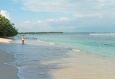 Giovane donna che cammina lungo la spiaggia tropicale Fotografie Stock