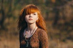 Giovane donna che cammina nel campo di erba secca dorato immagine stock libera da diritti