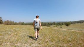 Giovane donna che cammina nel campo Movimento lento stock footage
