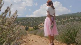 Giovane donna che cammina nel giacimento della lavanda video d archivio
