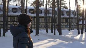 Giovane donna che cammina nel villaggio del cottage di inverno fra le betulle ed i pini Lustro del chiarore di Sun archivi video