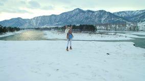 Giovane donna che cammina nella foresta nevosa archivi video
