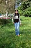 Giovane donna che cammina nella sosta Immagini Stock Libere da Diritti