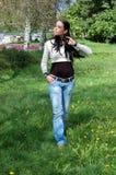 Giovane donna che cammina nella sosta Immagini Stock