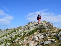 Giovane donna che cammina sull'alta montagna Ridge Fotografie Stock