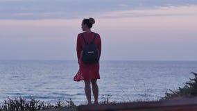 Giovane donna che cammina sulla spiaggia al crepuscolo archivi video