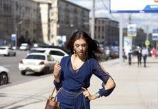 Giovane donna che cammina sulla via fotografia stock