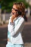 Giovane donna che cammina sulla via e che comunica sul telefono Fotografia Stock Libera da Diritti