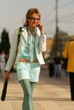 Giovane donna che cammina sulla via e che comunica sul telefono Immagini Stock