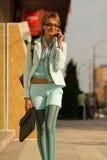 Giovane donna che cammina sulla via e che comunica sul telefono Fotografie Stock
