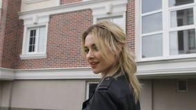Giovane donna che cammina sulla via Giri biondi che flirtano sguardo fisso con lo spettatore Rivestimento di cuoio nero video d archivio