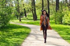 Giovane donna che cammina in una sosta Immagini Stock Libere da Diritti