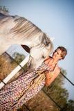 Giovane donna che cammina una strada con il cavallo Fotografie Stock Libere da Diritti