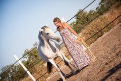 Giovane donna che cammina una strada con il cavallo Fotografia Stock