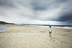 Giovane donna che cammina verso la linea costiera Immagine Stock