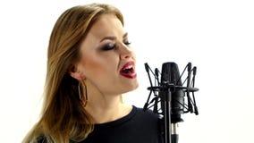 Giovane donna che canta con il microfono dello studio video d archivio