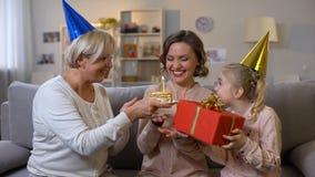 Giovane donna che celebra compleanno con la madre e la figlia, unità della famiglia archivi video