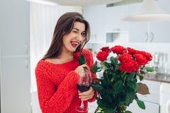 Giovane donna che celebra il mazzo della tenuta del giorno delle donne delle rose sulla cucina Vino bevente e sbattere le palpebr fotografie stock