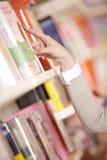 Giovane donna che cerca un libro Fotografie Stock Libere da Diritti
