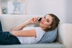 Giovane donna che chiama dal suo Smart Phone che si trova sul sofà Fotografia Stock
