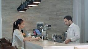Giovane donna che chiede barista maschio una fattura e che paga mentre sedendosi al contatore del caffè Fotografie Stock Libere da Diritti