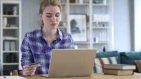 Giovane donna che compera online sul computer portatile, carta di credito stock footage