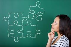 Giovane donna che completa puzzle Fotografia Stock Libera da Diritti