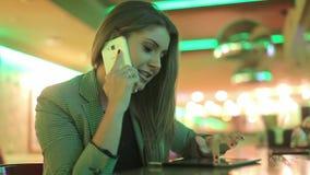 Giovane donna che comunica su un telefono delle cellule archivi video