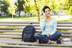 Giovane donna che comunica sul telefono e che sorride all'aperto Fotografie Stock Libere da Diritti