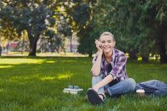 Giovane donna che comunica sul telefono e che sorride all'aperto Fotografia Stock
