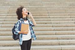 Giovane donna che comunica sul telefono e che sorride all'aperto Immagini Stock Libere da Diritti