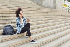 Giovane donna che comunica sul telefono e che sorride all'aperto Fotografia Stock Libera da Diritti