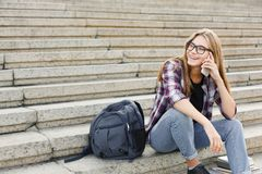 Giovane donna che comunica sul telefono e che sorride all'aperto Fotografie Stock