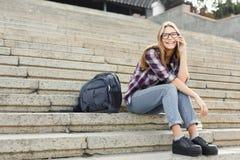 Giovane donna che comunica sul telefono e che sorride all'aperto Immagine Stock Libera da Diritti