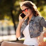 Giovane donna che comunica sul telefono Parco della città su fondo Immagine Stock