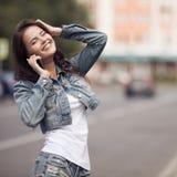 Giovane donna che comunica sul telefono Via della città su fondo Immagine Stock Libera da Diritti