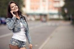 Giovane donna che comunica sul telefono Via della città su fondo Immagini Stock Libere da Diritti