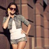 Giovane donna che comunica sul telefono Via della città su fondo Fotografia Stock